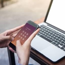 Frau mit Laptop und Smartphone in der Hand nutzt 2-Faktor-Authentifizierung als Schutz vor gehakten Social Media Accounts.