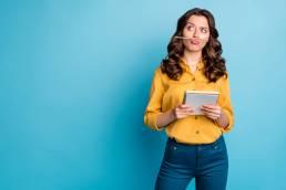 Junge Frau in gelber Bluse grübelt mit Stift und Block in der Hand über die richtige Formulierung der Instagram Bio