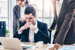 Drei Personen stehen um einen Laptop und diskutieren. Der Mann am Laptop sieht besorgt aus und hat die Hände vor dem Mund verschränkt.