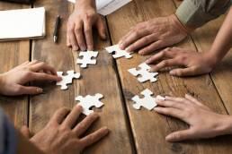 Sechs Hände legen auf einem Holztisch Puzzleteile zusammen. Als Social Media Team ergänzen sie sich perfekt, den jeder bringt individuelle Fähigkeiten mit.
